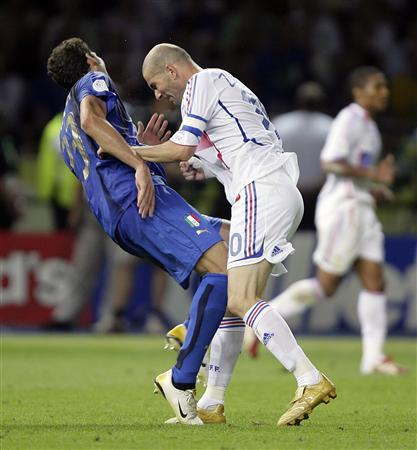 Italy's Marco Materazzi falls on the pitch after being head-butted by France's Zinedine Zidane (R) during the 2006 World Cup final in Berlin July 9, 2006. Materazzi is taking legal action against three British newspapers over their reporting of the incident in last July's World Cup final when he clashed with Zinedine Zidane, the BBC reported on Thursday. REUTERS/Peter Schols/GPD/Handout
