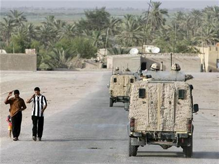 In this file picture, Iraqis exchanges greetings with British soldiers on patrol a few miles to the north of Basra, July 12, 2007. Britain should be in a position to hand over control of Basra to Iraqi forces before the end of the year, the head of the British military said on Thursday. REUTERS/Atef Hassan