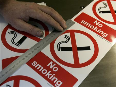 Printer Jason Hinks measures no smoking signs at First Safety Signs in Bishops Stortford, Hertfordshire, June 28, 2007. Only one person was fined for breaching the smoking ban in the two weeks after it came into force in England on July 1, the government said on Saturday. REUTERS/Luke MacGregor (BRITAIN)