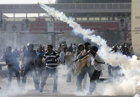 A protester throws back a tear gas canister at Malaysian riot police during a demonstration by ethnic Indians in Kuala Lumpur November 25, 2007.  REUTERS/Bazuki Muhammad