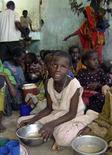 <p>Alcuni bambini ricevono razioni di cibo alla periferia di Mogadiscio. REUTERS PICTURE</p>
