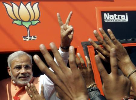 Gujarat's Chief Minister Narendra Modi shows a victory sign to his supporters during a road show for the assembly elections at Santroad, about 175 km east of Ahmedabad December 5, 2007. REUTERS/Amit Dave