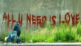 """<p>Una donna passa davanti a un muro con la scritta """"All you need is love"""". REUTERS/Toby Melville</p>"""
