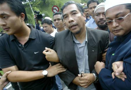 Treasurer of Malaysia's opposition Parti Islam se-Malaysia, Mohd Hatta Ramli, is arrested outside the parliament house in Kuala Lumpur December 11, 2007. REUTERS/Bazuki Muhammad