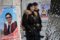 <p>Жители Бишкека проходят мимо предвыборных плакатов на улицах города, 14 декабря 2007 года. Оппозиционные партии в Киргизии в пятницу обвинили власти в попытке создать препятствия для их прохождения в парламент на досрочных выборах в воскресенье, а Центризбирком пожаловался на взлом его веб-сайта. (REUTERS/Vladimir Pirogov)</p>