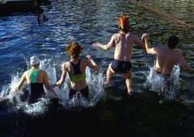 """<p>Partecipanti si buttano nel Loago Maggiore, a Locarno, per la tradizionale """"Nuotata della Befana"""". REUTERS/Fiorenzo Maffi(SWITZERLAND)</p>"""