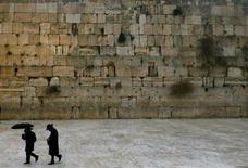 <p>Due ebrei ortodossi passano vicino al Muro Occidentale di Gerusalemme mentre scende la neve. REUTERS/Ronen Zvulun (JERUSALEM)</p>