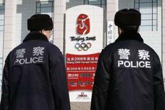 <p>Due poliziotti accanto al contatore che segna quanti giorni mancano all'inizio delle Olimpiadi di Pechino REUTERS/Claro Cortes IV</p>