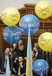 "<p>Спикер украинского парламента Яценюк (в центре) указывает на воздушные шары в здании Рады с надписями ""Скажем нет НАТО"". 12 февраля 2008 года. February 12, 2008. Opposition members protested against President Viktor Yushchenko's plans to seek NATO membership. REUTERS/Konstantin Chernichkin (UKRAINE)</p>"