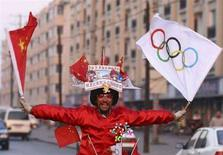 <p>Un tifoso sventola la bandiera cinese e quella delle Olimpiadi. REUTERS/Stringer</p>