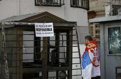 <p>Человек, накинувший на плечи флаг Сербии, стоит у посольства США в Белграде. В нападениях на иностранные посольства в Белграде, произошедших на этой неделе, виноваты США, заявил министр Сербии по Косово Слободан Самарджич, называя причиной поддержку США отделения Косово от Сербии. REUTERS/Stoyan Nenov</p>