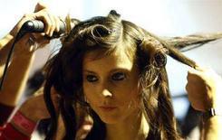 <p>Una modella con un'acconciatura nella foto d'archivio di una sfilata. REUTERS/Alessia Pierdomenico</p>