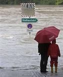 <p>Due persone in Austria osservano quella che era una strada prima di un'inondazione. REUTERS/Miro Kuzmanovic (AUSTRIA)</p>