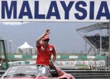 <p>Il pilota della Ferrari Kimi Raikkonen saluta la folla al GP della Malaysia. REUTERS/Bazuki Muhammad</p>