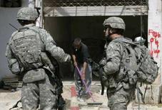 <p>Военнослужащие США осматривают место взрыва ракеты в Багдаде 23 марта 2008 года. Четверо военнослужащих США погибли в результате взрыва в Багдаде в воскресенье, доведя, таким образом, численность потерь американских военных в Ираке до 4.000 человек. (REUTERS/Ceerwan Aziz)</p>