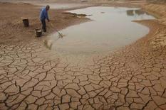 <p>Un uomo raccoglie dell'acqua da uno stagno in secca a Yingtan, nella provincia cinese di Jiangxi. REUTERS/Stringer (CHINA)</p>