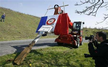 A forklift decorated with a French flag removes the sign bearing the community name Champagne at the entrance of the village of Champagne, west of Geneva April 5, 2008. Swiss wine-growing community of Champagne vowed on Saturday to continue its fight to use the name of the village to label its production. REUTERS/Denis Balibouse