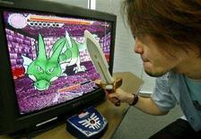 """<p>Il produttore di videogame Ryutaro Ichimura cerca di battere il dragone del gioco """"Kenshin Dragon Quest"""" con una spada wireless. REUTERS/Eriko Sugita ES/RCS</p>"""