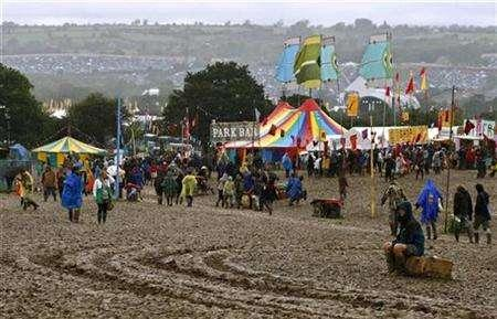 Revellers walk through a muddy field during the Glastonbury music festival in Somerset, south-west England, June 24, 2007. Every morning, the head of Britain's Glastonbury Festival swims 40 laps of a chilly pool. But sales of tickets for this year's show aren't performing quite so swimmingly. REUTERS/Dylan Martinez