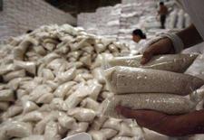 <p>Рабочий держит пакеты с рисом на складе в Маниле, 14 апреля 2008 года. Высшие представители Международного валютного фонда и Всемирного банка в воскресенье потребовали немедленных действий для остановки растущих цен на продовольствие, предупредив, что социальное напряжение может усилиться, если стоимость основных продуктов питания не будет снижена. (REUTERS/Romeo Ranoco)</p>