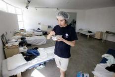 <p>L'artista Akim One Machine-Tu Nyuyen indossa una cuffia mentre mangia al Museo di Bat Yam vicino a Tel Aviv. REUTERS/Baz Ratner</p>