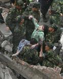 """<p>Солдаты китайской армии достают из-под завалов пострадавших в результате землетрясения, округ Бэйчуань, Китай, 13 мая 2008 года. исло погибших в результате разрушительного землетрясения на юго-западе Китая выросло до 14.866 человек, сообщило китайское информагентство """"Синьхуа"""".(REUTERS/Stringer)</p>"""