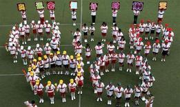 <p>Il logo delle Olimpiadi formato da tanti ragazzini durante una manifestazione per celebrare i 100 giorni ai Giochi di Pechino il 30 aprile. REUTERS/China Daily</p>