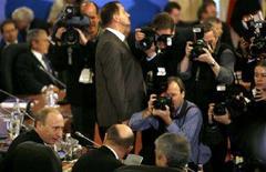 <p>Премьер-министр РФ Владимир Путин в центре внимания представителей СМИ в Бухаресте 4 апреля 2008 года. Московский офис Русской медиагруппы обыскали сотрудники управления борьбы с экономическими преступлениями, сообщил в среду вечером ряд российских СМИ. (REUTERS/Kevin Lamarque)</p>