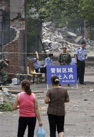 Military and police personnel guard the entrance to the Juyuan Middle School where about 280 children died in last month's earthquake, in Juyuan town near Dujiangyan city in Sichuan province June 12, 2008. The sign reads: ''Restricted area. No entry.'' REUTERS/David Gray