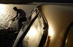 <p>Immagine d'archivio di un uomo che raccoglie dell'acqua accanto alla sua macchina. REUTERS/Ahmad Masood (AFGHANISTAN)</p>