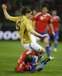 <p>Испанец Фернандо Торрес (вверху) борется за мяч с французом Лилиамом Тюрамом в товарищеском матче в Малаге 6 февраля 2008 года. Сборная Испании по футболу не переживает по поводу того ,что в полуфинальном поединке с командой России ей придется играть в несчастливых желтых футболках. (REUTERS/Marcelo del Pozo)</p>
