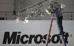 <p>Un uomo monta le luci di uno stand Microsoft in occasione della fiera di Hannover. REUTERS/Hannibal Hanschke (GERMANY)</p>