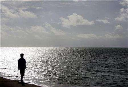 A boy walks in front of the sea in Key West, Florida, October 20, 2005. REUTERS/Carlos Barria