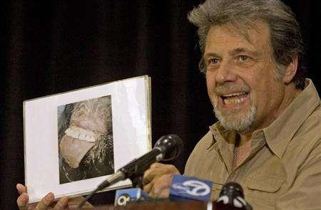 Tom Biscardi, CEO and founder of BIGFOOT Inc., holds up a picture he claims is the mouth of Bigfoot in Palo Alto, California, August 15, 2008. Bigfoot, also known as Sasquatch, is a mythical ape-like creature said to live in forests of the Pacific northwest region of the United States. REUTERS/Kimberly White
