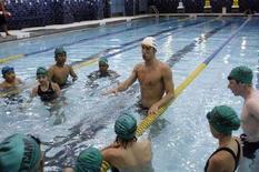 <p>Michael Phelps mostra esercizi per il nuoto ad alcuni bambini. REUTERS/Joshua Lott (UNITED STATES)</p>