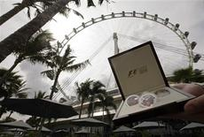 <p>A model holds a set of Formula One commemorative coins in front of the Singapore Flyer observation wheel during its presentation September 10, 2008. REUTERS/Pablo Sanchez</p>