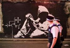 <p>Policemen look at a mural by graffiti artist Banksy painted on the wall of a tunnel near Waterloo Station in London, June 23, 2008. REUTERS/Finbarr O'Reilly</p>
