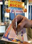 """<p>A customer selects numbers on a """"EuroMillions"""" lottery ticket in a tobacconist shop in the small village of Truchtersheim near Strasbourg, France, February 2, 2006. REUTERS/Vincent Kessler</p>"""