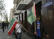 <p>Men carrying the Chechen flag walk past a Putin Avenue street sign in Grozny October 5, 2008. A central avenue in the capital of Russia's Chechnya region, Grozny, was named after Vladimir Putin on Sunday, honouring the man who sent in troops to crush a separatist rebellion there. REUTERS/Said Tsarnayev</p>
