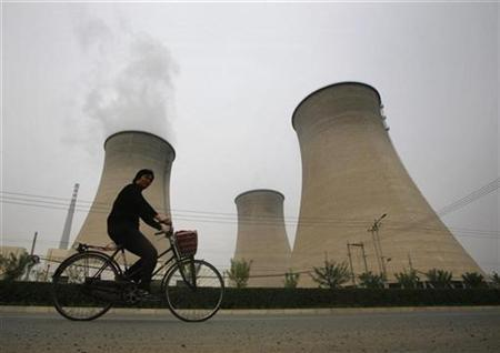 A woman rides her bicycle past the cooling towers of a coal-burning power station on a hazy day in Beijing October 21, 2008. REUTERS/David Gray