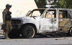 <p>Иракский полицейский осматривает сгоревший автомобиль на месте взрыва бомбы экстремистом-смертником в Багдаде 23 октября 2008 года. Одиннадцать человек погибли и 22 были ранены в результате подрыва экстремиста-смертника, въехавшего в автомобиле в кортеж министра труда Ирака в центре города в пятницу. REUTERS/Ceerwan Aziz (IRAQ)</p>