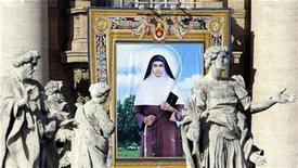 <p>A tapestry depicting Sister Alphonsa of the Immaculate Conception is seen among the statues of St. Peter's Colonnade during the canonization ceremony led by Pope Benedict XVI in St. Peter square at the Vatican October 12, 2008. REUTERS/Alessandro Bianchi</p>