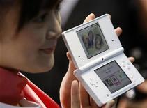 <p>Foto de archivo de una modelo junto a una consola Nintendo DS en una conferencia de prensa en Tokio, 2 oct 2008. El fabricante japonés de videojuegos Nintendo lanzará probablemente un nuevo modelo de su consola portátil líder en ventas DS en el mercado internacional en el verano del 2009, dijo el viernes su presidente, Satoru Iwata. REUTERS/Kim Kyung-Hoon</p>