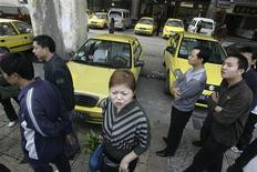 <p>Residents and taxi drivers stand beside a row of taxis parked along a street in Chongqing municipality November 3, 2008. REUTERS/Stringer</p>