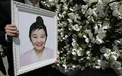 <p>Anthony Cheung, godson of Nina Wang, carries a portrait of Wang at a crematorium during Wang's funeral in Hong Kong April 18, 2007. REUTERS/Paul Yeung</p>
