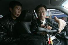 <p>Moon Sung-ok (R), president and teacher at a paparazzi school, shows a student how to use a hidden camera during training in a car in Seoul November 15, 2008. 2008. REUTERS/Jo Yong-Hak</p>