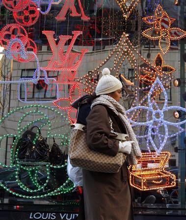 A shopper passes a window display at high-end luxury goods maker Louis Vuitton along 5th Avenue in New York, November 19, 2008. REUTERS/Mike Segar
