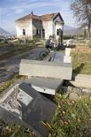 <p>A boy rides his bike through a partially destroyed Serbian Orthodox cemetery is seen in the ethnically divided town of Mitrovica in this November 13, 2008. REUTERS/Adam Tanner</p>