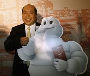 <p>Chan Yan-tak, chief chef of Lung King Heen, poses with a cutout of Bibendum or the Michelin Man mascot, during a party celebrating the release of the first edition of the 'Michelin guide Hong Kong Macau' in Hong Kong December 2, 2008. REUTERS/Bobby Yip</p>