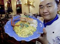 <p>A chef at Bangkok's Blue Elephant restaurant, which also conducts traditional Thai cooking classes, shows a creation featuring a giant shrimp in this September 6, 2002 file photo. REUTERS/Sukree Sukplang/Files</p>